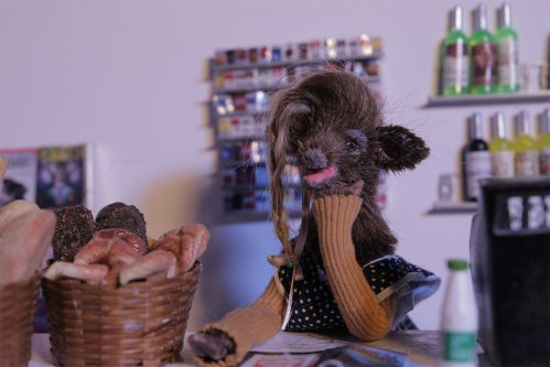 A female model of a deer, taken as a still from a stop motion animated film, sits in a bakery alongside some pastries.