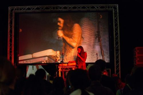 A photograph from behind a crowd watching a woman sing into a microphone on a stage, an image of her is projected onto a large screen above the stage