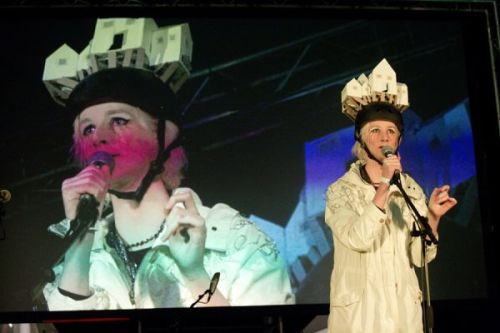 Photograph of someone performing on stage, wearing a hat made of miniature houses