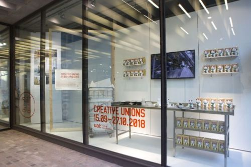 Photograph of the window gallery from outside, showing the installed exhibition through the glass, which is made up of a television mounted at the back and a table displaying objects