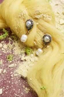 Work by Visual Merchandising - Interiors students, taken by Sarah Manning. Pearl earrings pinned to a yellow hair like material with scattered crushed concrete below.