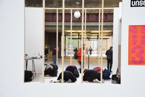 People lying on floor within replica room space