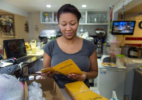 Jennifer, an employee of La Barra restaurant, receives the new Spanish and English menus.