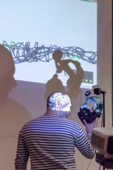 A person holding a pair of headphones in front of a projector.