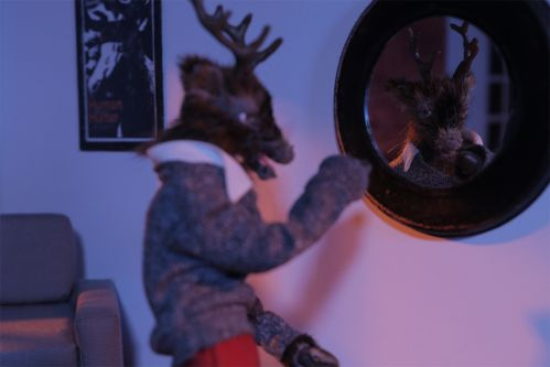 A male model of a deer, taken as a still from a stop motion animated film, waves to another deer in a shop scene, looks in a mirror with a scary face looking back.