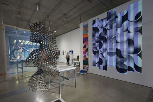 Photograph of the gallery with several pieces of artwork installed. a sculpture hangs from the ceiling in the middle and an image of a lilac and green absract pattern hangs on the wall behind it
