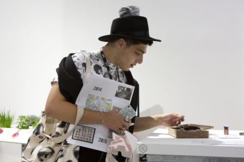 Photograph of someone in a black hat, holding a publication in one arm and looking at artwork, objects displayed on a table