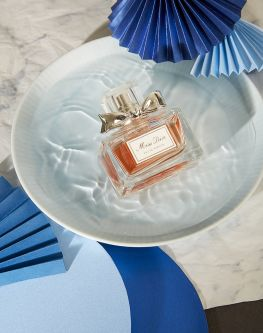 Work by Visual Merchandising - Interiors students, taken by Sarah Manning. A perfume bottle sat in a bowl of water surrounded by blue fans.