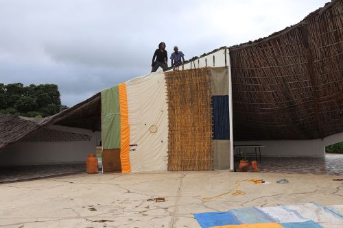 side of makeshift building with people standing on the roof