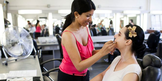 A young woman doing the make up of another woman