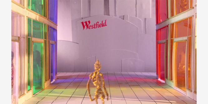 film still of human figure made out of metal wire whilst standing in multicoloured shopping centre looking at sign reading Westfield