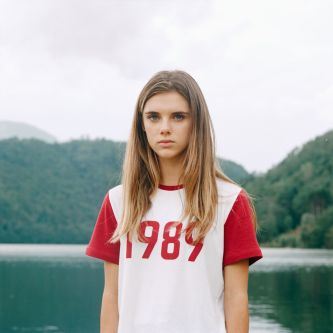 Portrait of adolescent girl with long blonde hair and a t-shirt with slogan '1989' in front of a picturesque lake