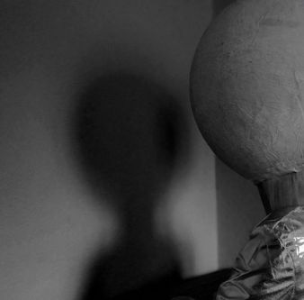 black and white photo of person with large ball on head standing in front of white wall - shadow play