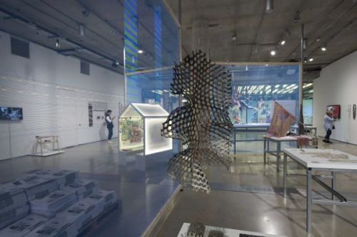 Photograph of the gallery and the exhibition picturing a several sculptures installed, one hanging from the ceiling at the front alongside work displayed on tables