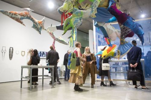 Photograph of people in the gallery socialising and looking at the artwork, a soft sculpture hangs from the ceiling in the foreground and the photograph is taken from a low angle