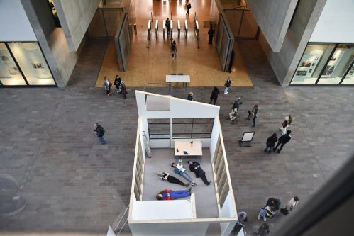 Replica structure of room seen from above with people lying on its floor