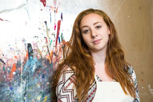Headshot of Emma in the Summer Study Abroad Textile Design Workshop, in front of a colourful wall