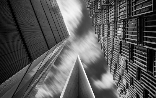 Black and white photograph showing a shot upwards at three high-rise buildings.
