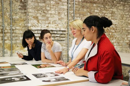Schelay McCarter working with students, looking at photographs of fashion models.