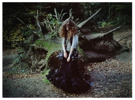 Fashion photograph of a model in a wooden area wearing a mask and a dark purple velvet skirt.