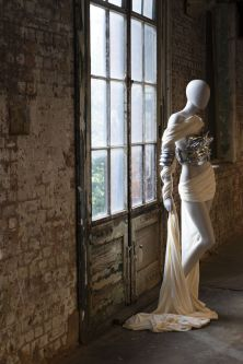 Mannequin in white and silver outfit next to a window
