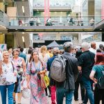 Photograph of people socialising at the degree show in a large group, above them in the background people stand looking out over a walkway