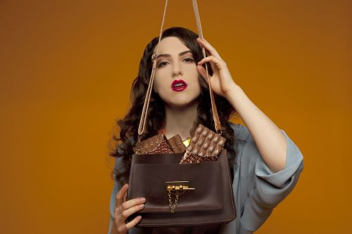 Model holding brown bag on orange background