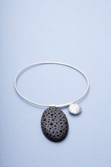 Sarah King's jewellery design, pebble and silver sphere shapes on a bangle.