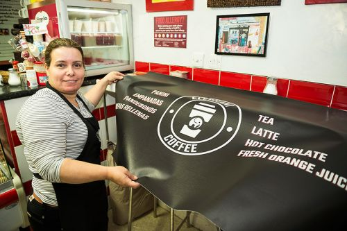 Esmeralda receiving her new design in her Colombian Café shop, Elephant Coffee located on Elephant Road.