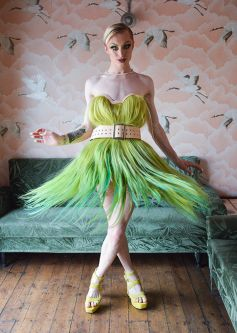 Model in a green hair dress with white belt
