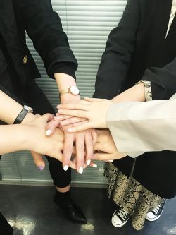 Student bonding exercise, students have placed hands of top of each other.