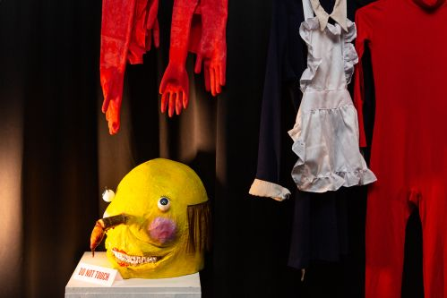 Props for a student animation, including a yellow head, hangin red gloves and a red body suit.