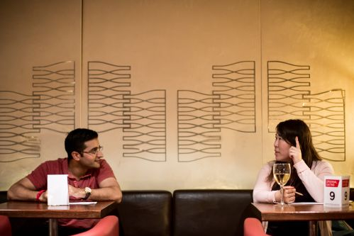a man and woman talking across tables