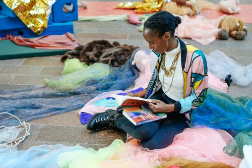 Rochelle Saunders reading a book among fabrics and creative materials.
