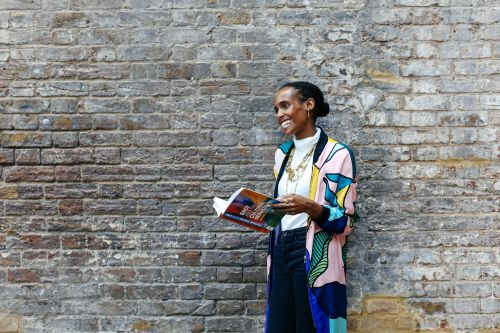 Rochelle Saunders standing in front of a brick wall holding a book and laughing.