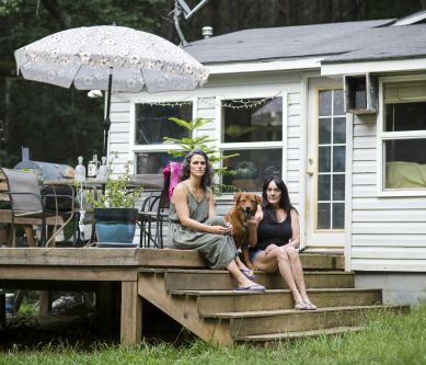 two women sat on steps outdoor a house