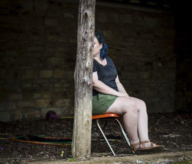 a woman sat behind a tree