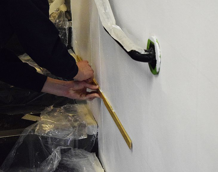 A close up image of a white wall with two hands holding a ruler and a pencil to start ruling out the grid for the wall mural