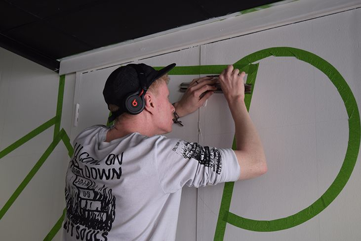 Kyulx placing green masking tape on to the wall to outline the geometric shapes for the wall mural