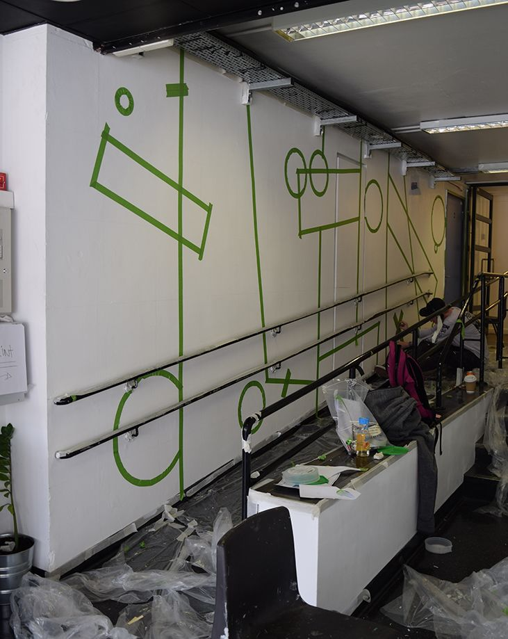 The left hand side wall in white with green masking tape placed for the geometric shapes