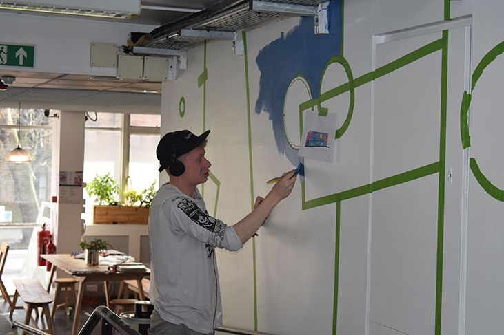 Kyulx begins painting in blue around the green masking tape