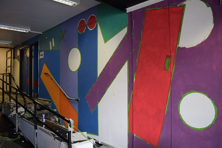 One section of the right hand side of the wall. The basic block colours of blue and purple are complete with orange and red rectangles cutting into the main blocks. White circles and a large white rectangle still awaits painting