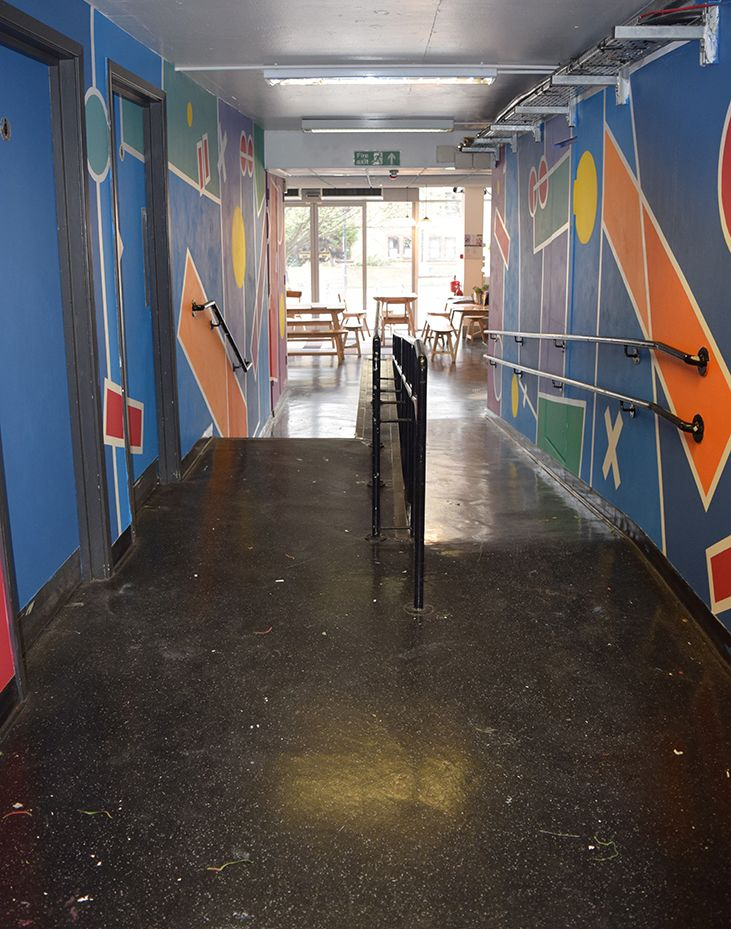 Looking down the corridor with either wall fully painted in blues and purples with geometric shapes cutting into the main blocks in red, yellow, green and orange
