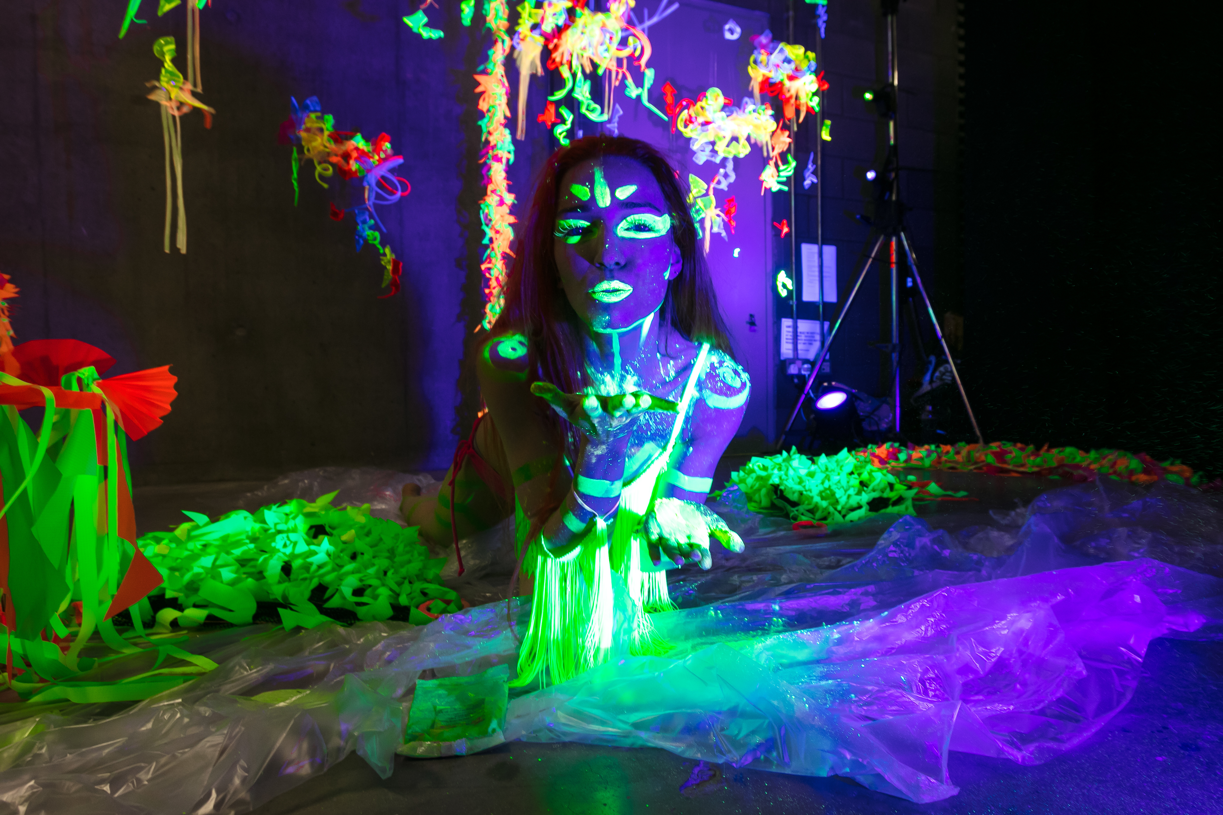 Darkened room with person covered in glow-in-the-dark decoration