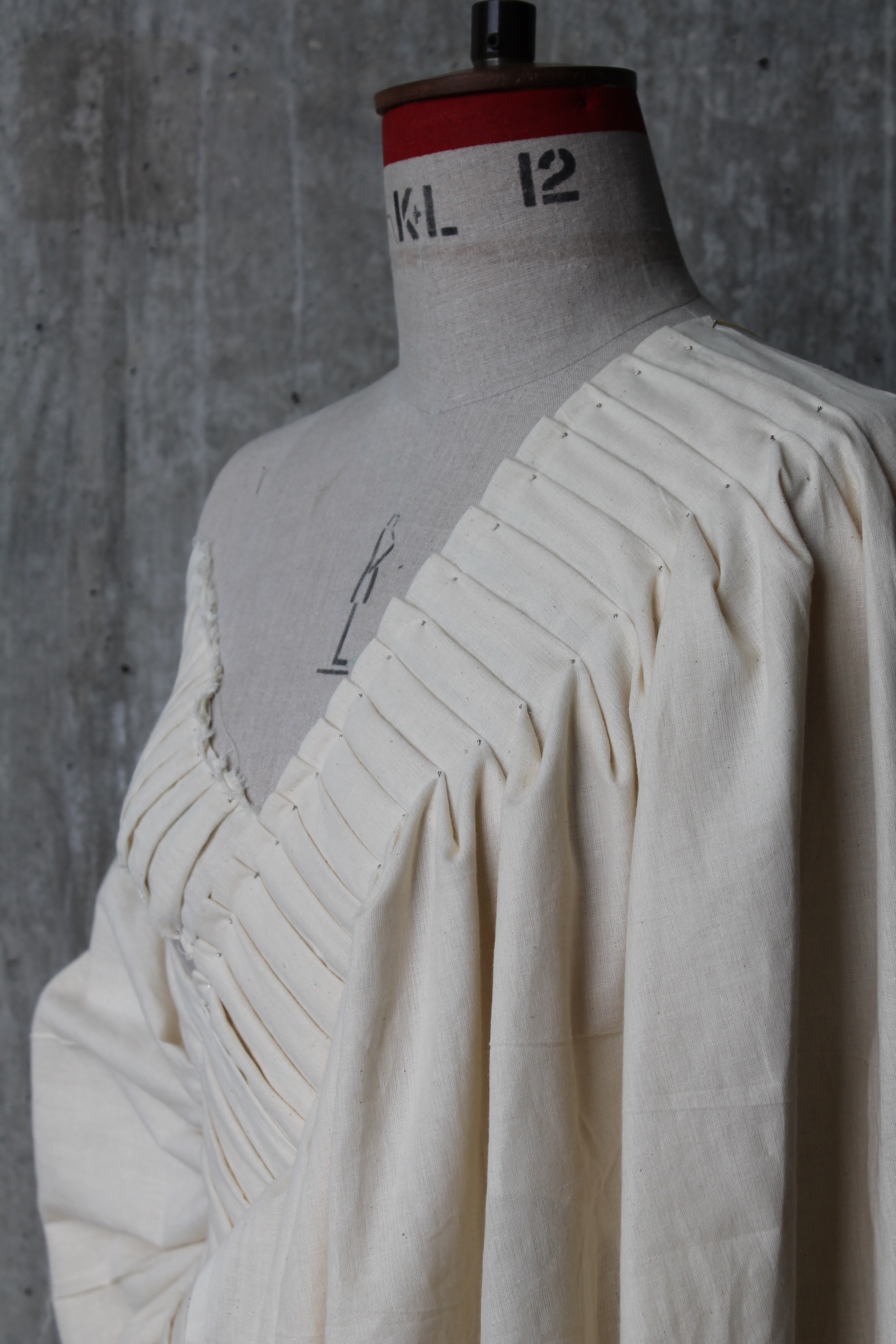 a studio shot of a wide-necked, cream coloured garment on a mannequin