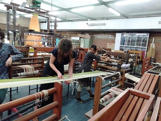 Students working with weaving equipment