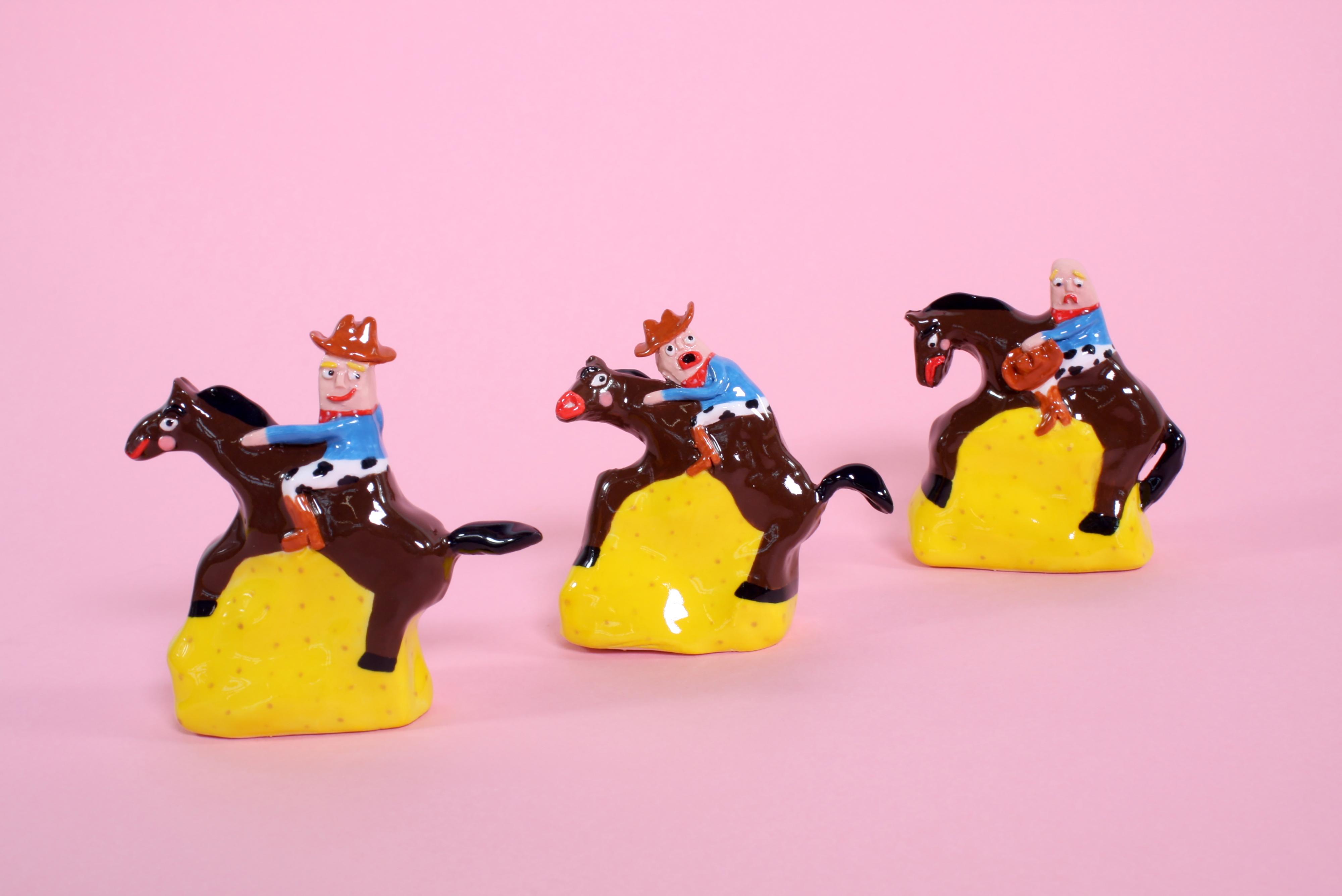 three ceramic cowboys on horses