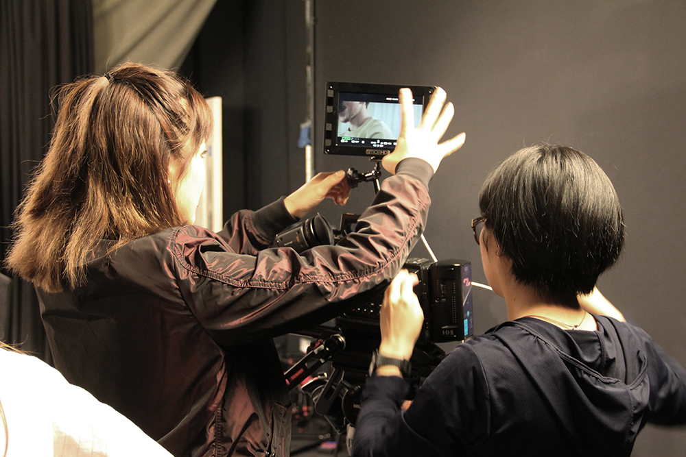 Students in TV studio, using camera