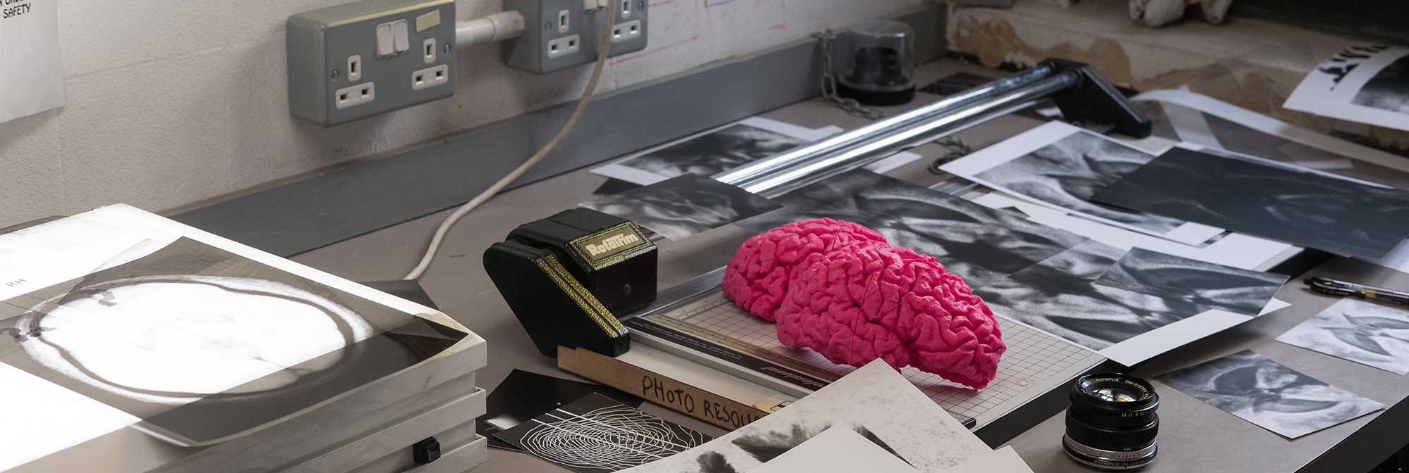 A bright pink model of a brain sits on a desk next to scanning equipment, a guillotine and a black and white print out of a brain scan.