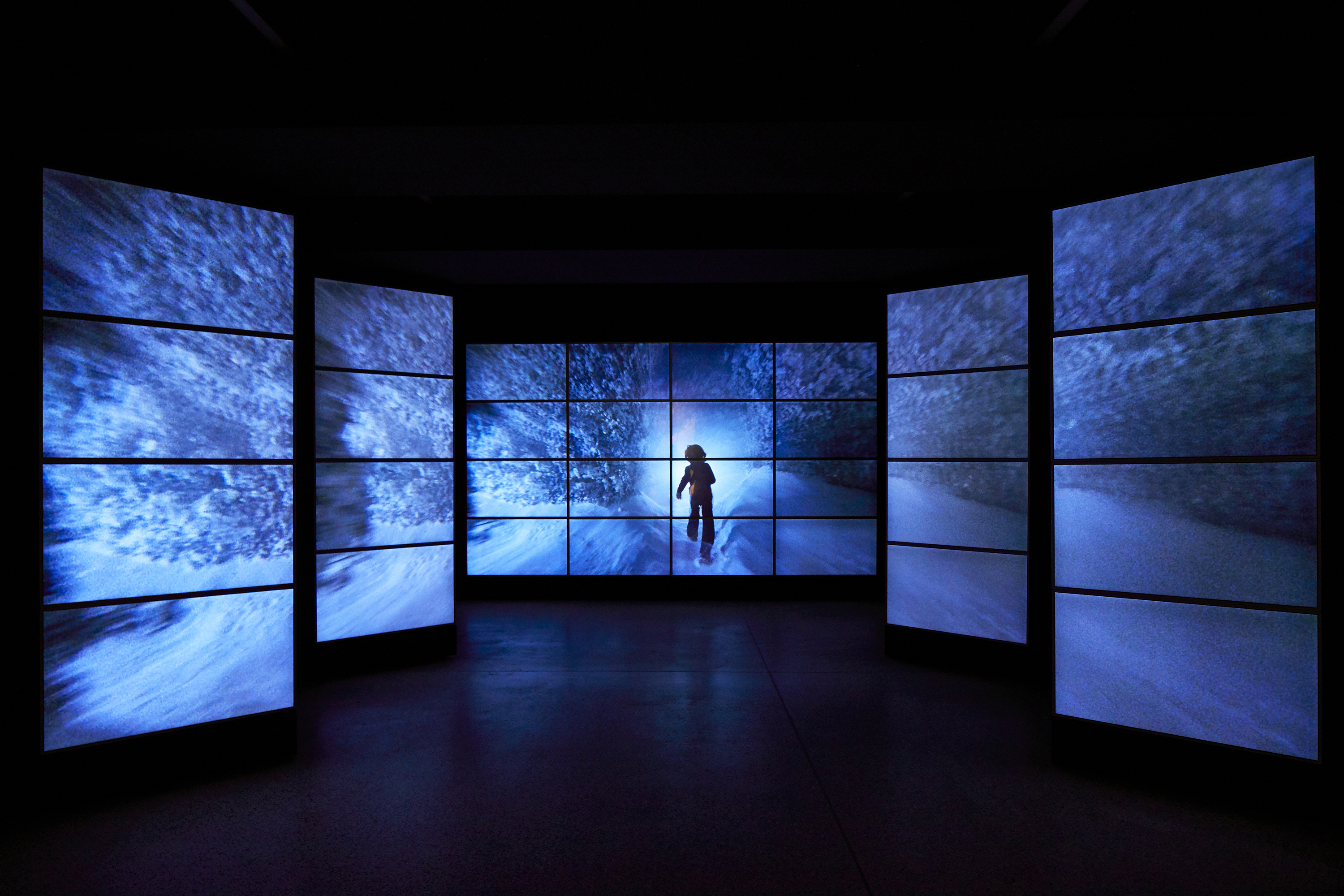 An image showing the entrance to the exhibition, flanked by video screens exhibition